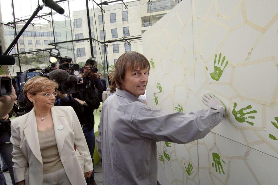 Nicolas Hulot signe un mur blanc de l'empreinte de sa main, au côté de la présidente de l'Agence de l'environnement et de la maîtrise de l'Energie (Ademe) Michèle Pappalardo, le 24 mai 2005 à Paris. Il espère «créer un élan citoyen» en invitant les Français à s'engager contre le changement climatique à travers dix gestes du quotidien.