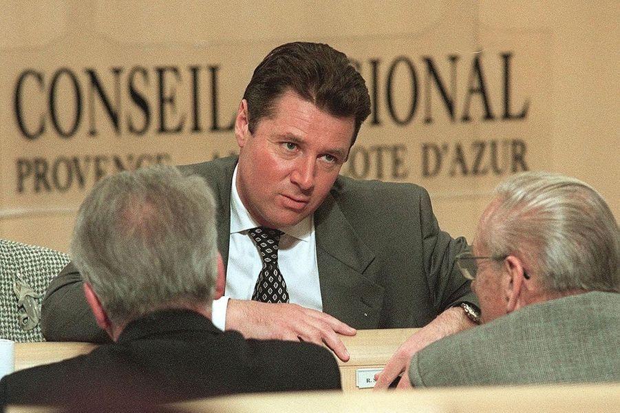 Christian Estrosi (C), président du groupe UDF de la Région Provence-Alpes-Cote-d'Azur s'entretient avec des conseillers régionaux de sa formation dans l'hémicycle du Conseil régional, le 20 mars 1998.
