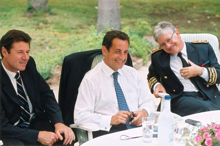 Nicolas Sarkozy à la préfecture d'Ajaccio : lors d'une pause dans les jardins, le ministre de l'Intérieur assis en compagnie du préfet de Corse Pierre-René Lemas et du ministre délégué à l'Aménagement du territoire Christian Estrosi, tous trois souriant en 2005.