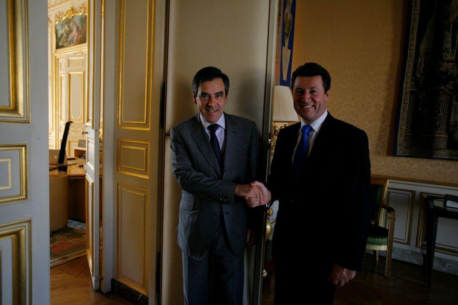 François Fillon échangeant une poignée de mains avec le nouveau ministre de l'Industrie Christian Estrosi dans un bureau de Matignon en 2009.