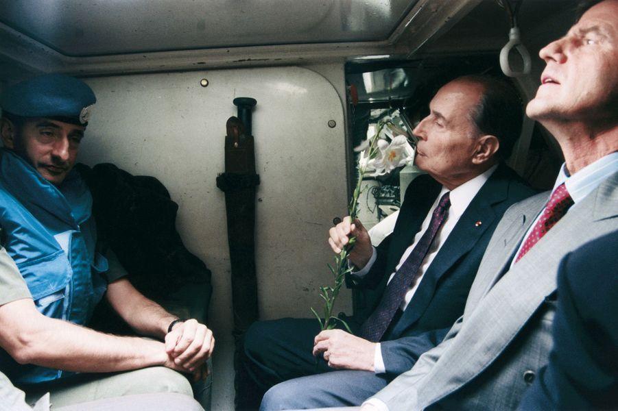 A Sarajevo, le 28 juin 1992, François Mitterrand respire l'odeur d'un lys qu'une femme inconnue, mêlée à la foule, vient de lui offrir. A sa gauche, Bernard Kouchner.