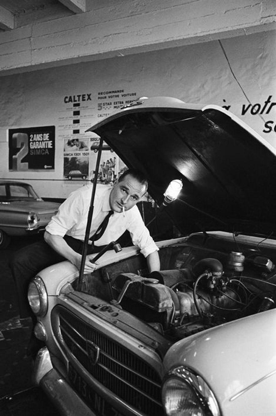 Jacques Chirac, nouveau ministre du Travail, bricole le moteur de sa voiture la Peugeot 403