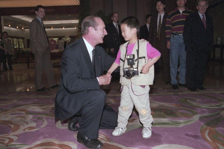 Lors d'un voyage à Shanghai, Jacques Chirac en admiration d'un petit garçon, petit reporter avec son appareil photo, mai 1997