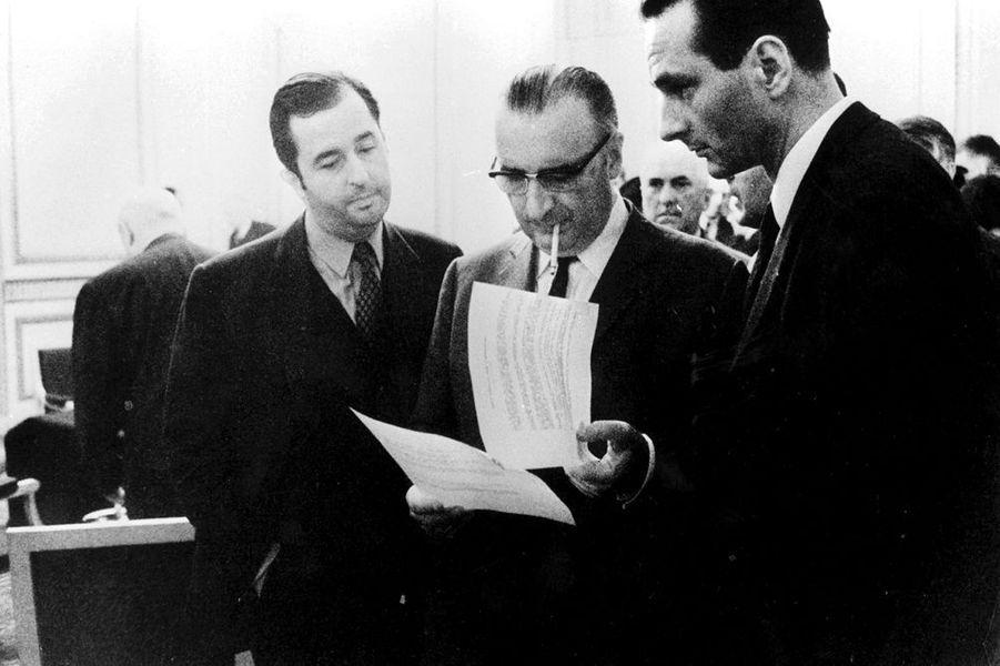 Samedi 25 mai 1968, le Premier ministre Georges Pompidou lit des papiers entourés de Jacques Chirac et d'Edouard Balladur