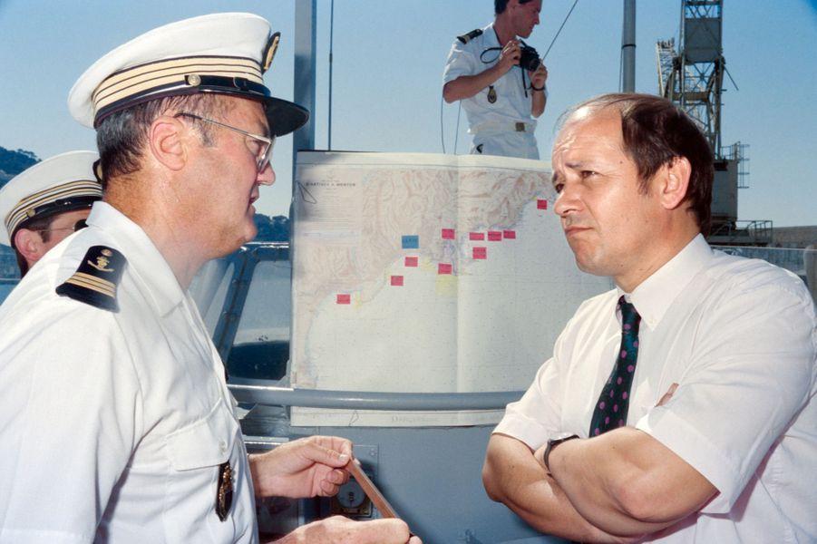 Le secrétaire d'état à la mer Jean-Yves Le Drian (D) discute avec un membre de la police maritime chargé du contrôle des plaisanciers, le 3 août 1991.