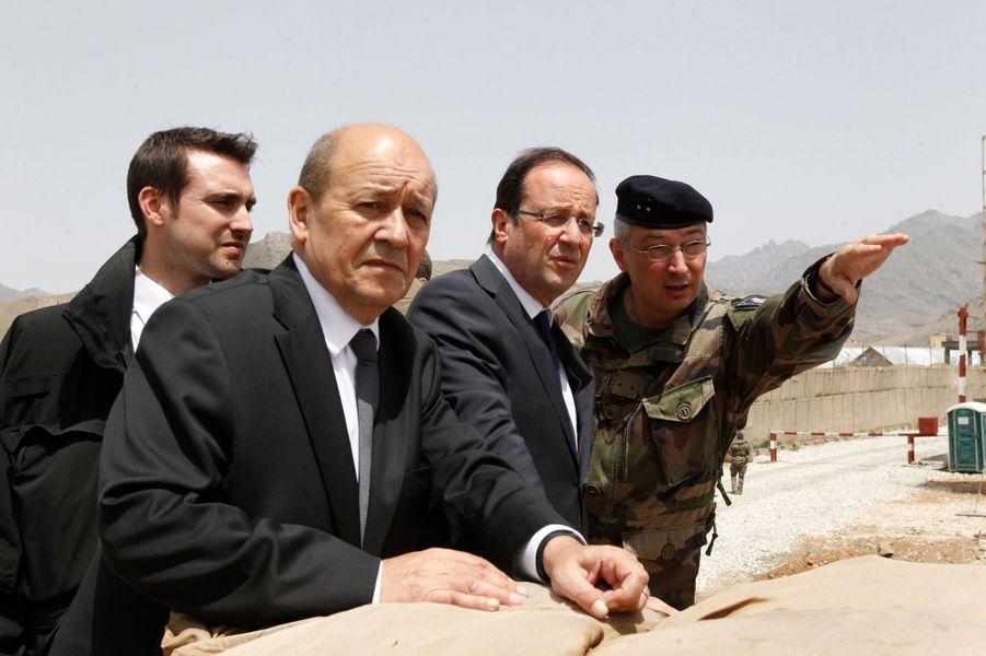 """Le 25 mai 2012, le président François HOLLANDE a effectué une visite éclair de six heures en Afghanistan, pour """"expliquer lui-même"""" aux soldats français les raisons du retrait anticipé des troupes. Ici, à un poste de guet sur la base de Nijrab, avec le ministre de la Défense Jean-Yves LE DRIAN et le général Eric HAUTECLOQUE-RAYSZ, à la tête de la brigade La Fayette. Derrière eux se tient un garde du corps."""