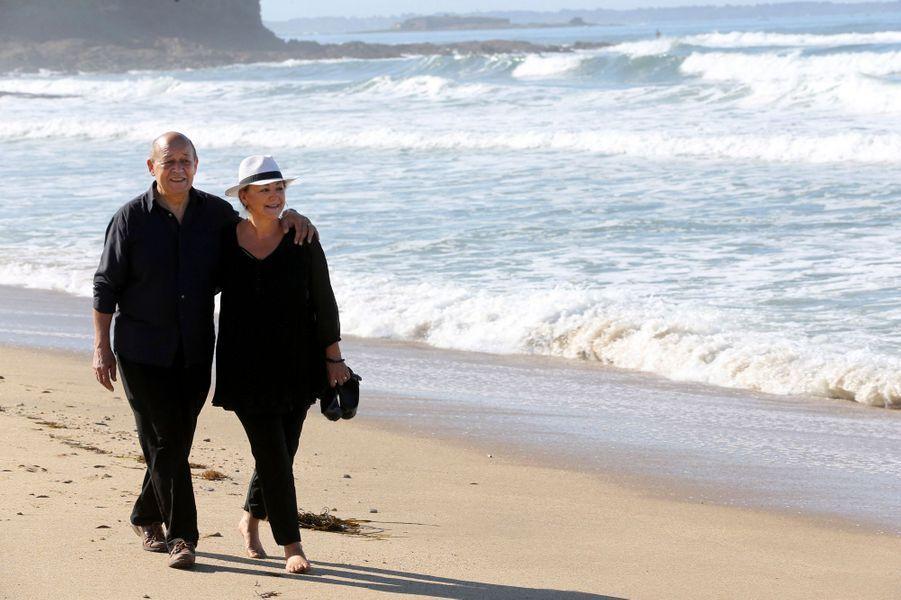 Promenade en amoureux pour Jean-Yves LE DRIAN et son épouse Maria VADILLO, pieds nus, ses chaussures à la main, sur la plage de GUIDEL dans le Morbihan le 8 août 2015.