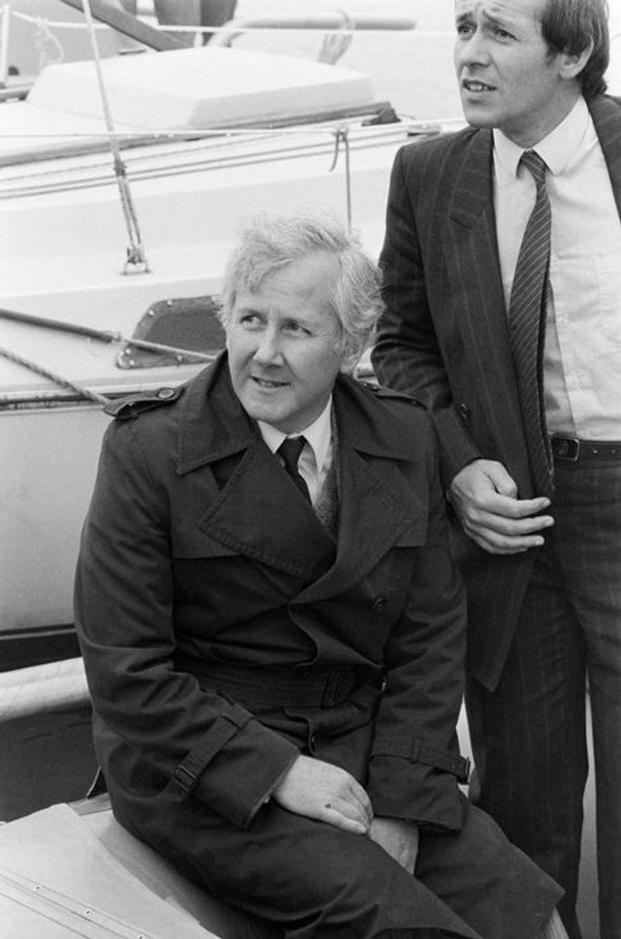 Lorient - 20 mai 1983 - Dans un port, lors de la préparation du voilier PAUL RICARD du navigateur Eric TABARLY, avant le départ de la 2e transat en double Lorient - les Bermudes - Lorient : Guy LENGAGNE, secrétaire dEtat aux transports, assis sur le pont du bateau, en compagnie de Jean-Yves LE DRIAN, maire de la ville.