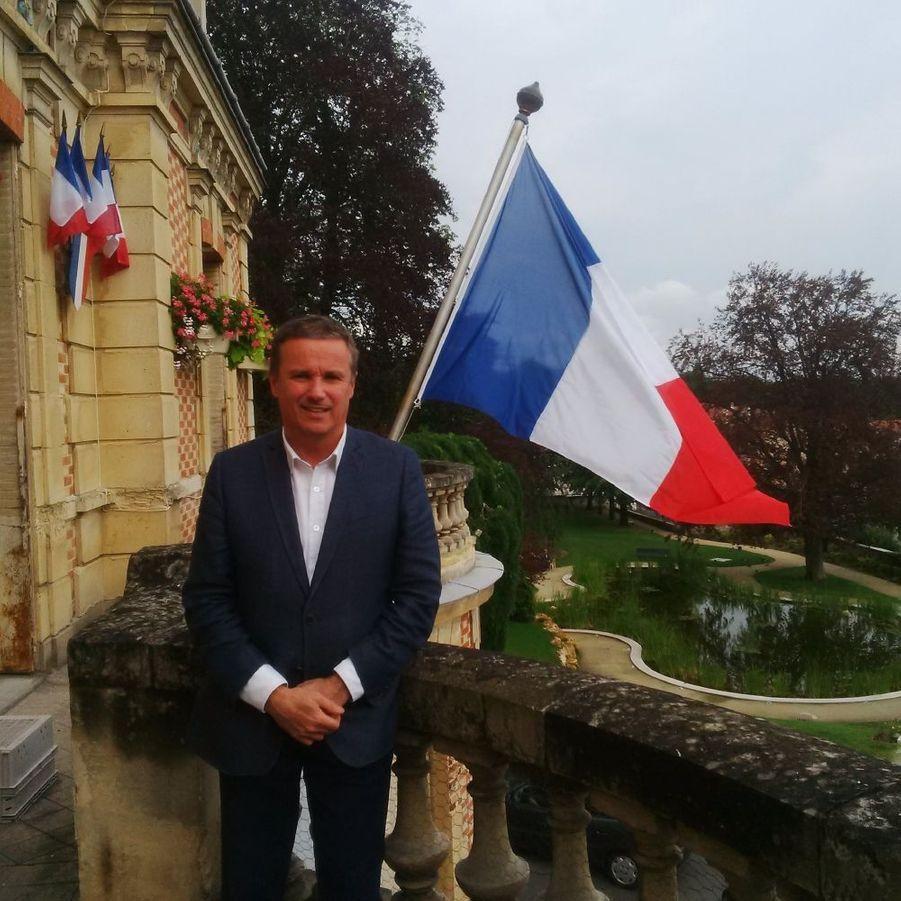 Nicolas Dupont-Aignan, député de l'Essonne et président de Debout la République, pose devant le drapeau de sa mairie de Yerres.
