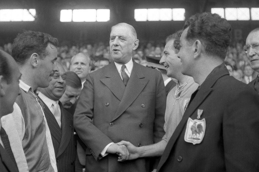 Le Général Charles De Gaulle salue le capitaine du Havre André Strappe et le capitaine de Sochaux René Gardien à l'issue de la finale de la Coupe de France, le 03 mai 1959. Cette rencontre s'étant terminée par un match nul, les équipes rejoueront le 18 mai 1959 avec une victoire du Havre 3 à 0.