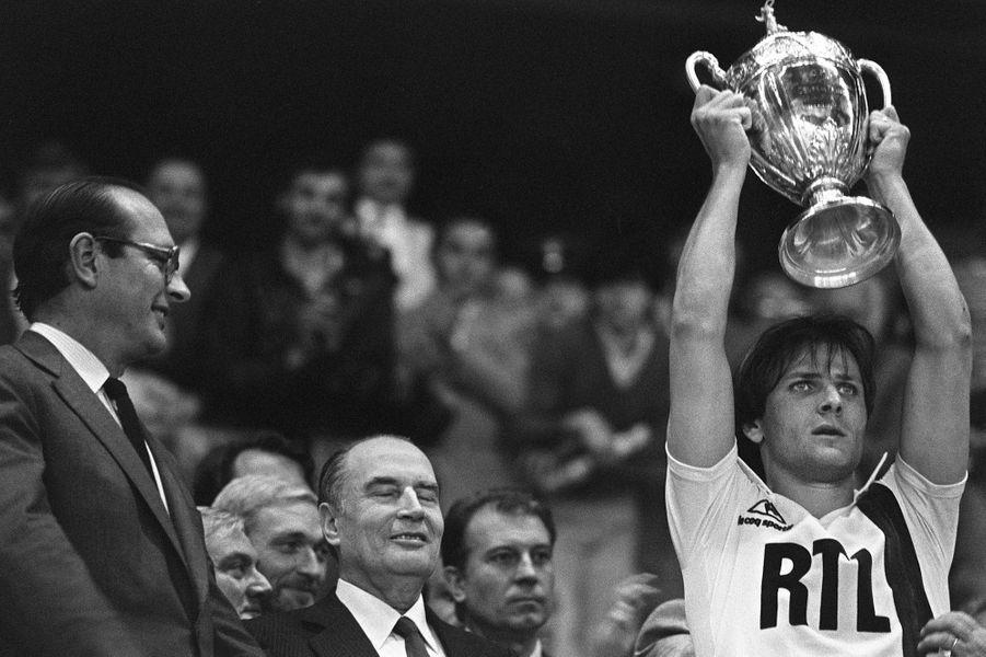 Dominique Bathenay (droite), le capitaine du Paris Saint-Germain brandit la Coupe de France qu'il vient de remporter avec son équipe, le 15 mai 1982 au parc des Princes, sous le regard de Jacques Chirac, maire de Paris, et François Mitterrand, président de la République. Le Paris Saint-Germain a battu Saint Etienne 2 à 2, 6 pénalties à 5.