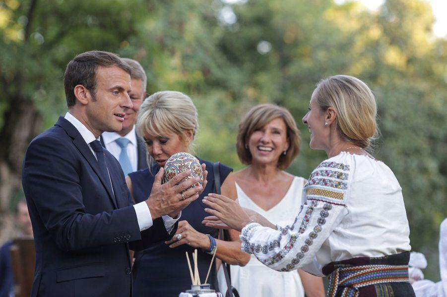 Emmanuel Macron reçoit un oeuf d'autruche peint lors de sa visite dumusée du village roumain «Dimitrie Gusti»..
