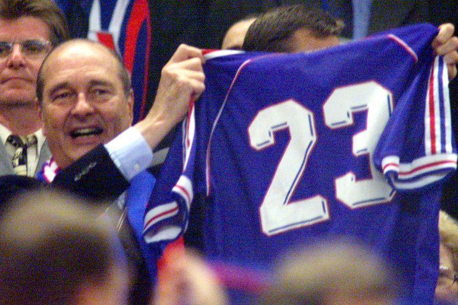 Le 23e homme, c'est lui. Jacques Chirac brandit fièrement le maillot n°23 en tribune présidentielle le 12 juillet 1998.