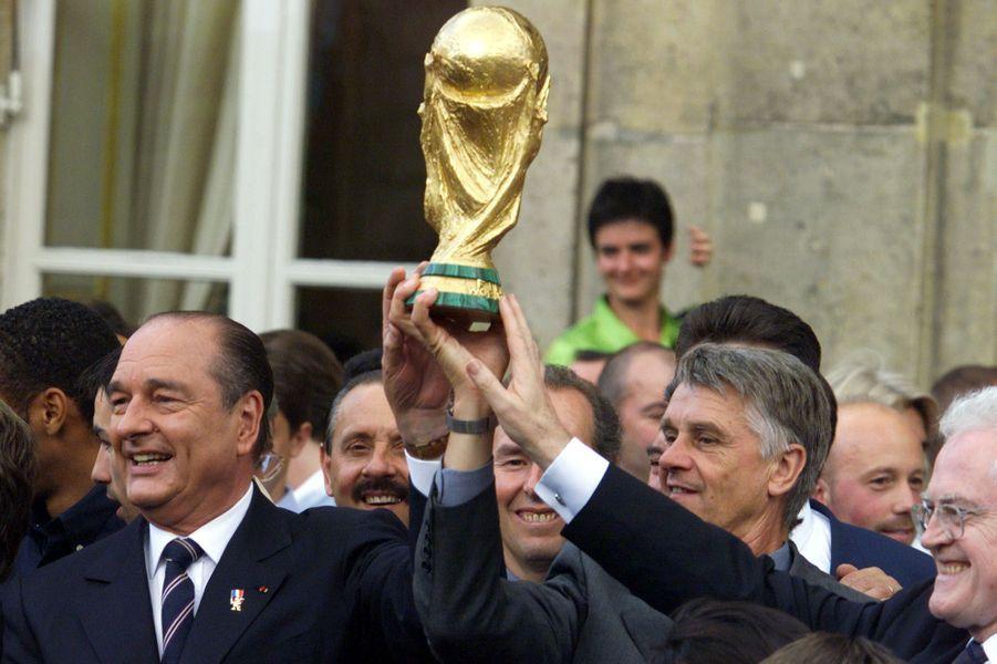 Garden party mémorable à l'Elysée. Jacques Chirac, Aimé Jacquet et Lionel Jospin brandissent la Coupe du monde.