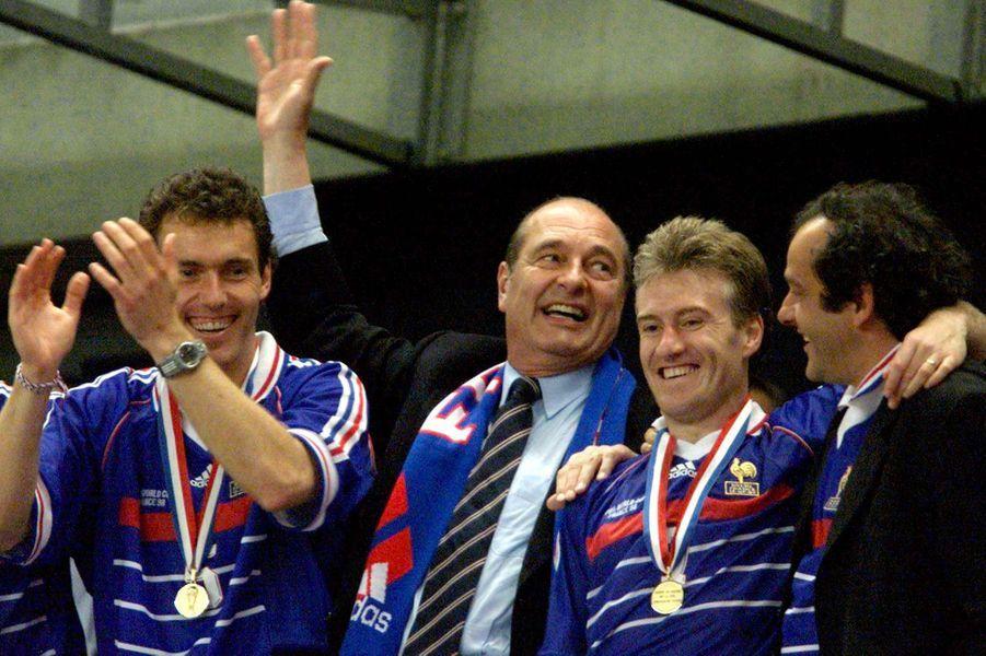 Les Bleus sont champions du monde. Jacques Chirac fête l'évènement avec Didier Deschamps, Laurent Blanc et Michel Platini.