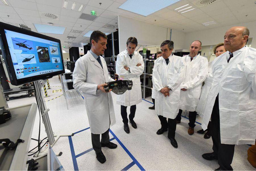 François Fillon et Alain Juppé, en blouses blanches, écoutent les explications d'employés du groupe Thalès.