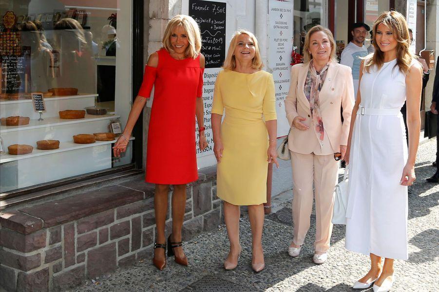 Brigitte Macron et les conjointes des participants au G7 à Espelette devant une pâtisserie, dont la spécialité est le gâteau basque.