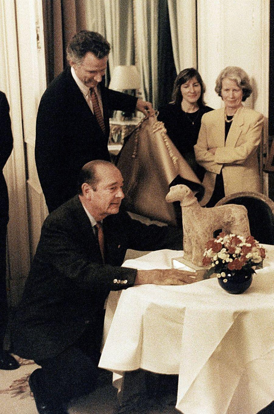 29 novembre 1996. Pour le 64ème anniversaire de Jacques Chirac, son épouse Bernadette et ses collaborateurs à l'Elysée lui ont préparé une surprise en lui offrant une sculpture africaine du XIIème siècle trouvée au Mali, un bélier en terre cuite. Le président est accroupi devant son cadeau, en présence de son épouse et de ses collaborateurs dont Dominique de Villepin. On reconnaît également Pierre de Bousquet de Florian à gauche, Irène Battistelli.