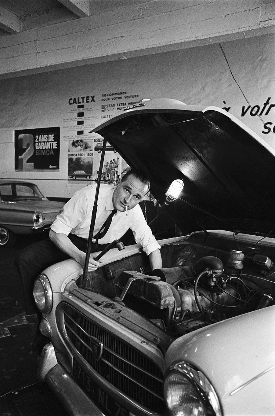 14 avril 1967.Jacques Chirac, nouveau ministre du Travail, fumant une cigarette en bricolant dans le moteur de sa voiture modèle Peugeot 403, dans un garage.
