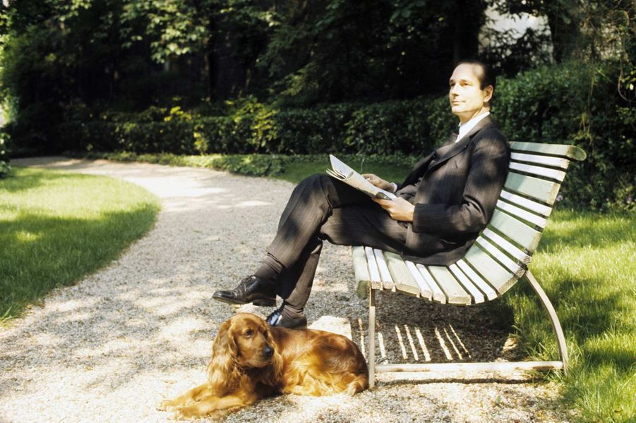Dans les jardins de Matignon, le nouveau Premier ministre Jacques Chirac, qui a pris ses fonctions le 27 mai 1974, en costume cravate, assis sur un banc avec un journal, son chien cocker couché près de lui.