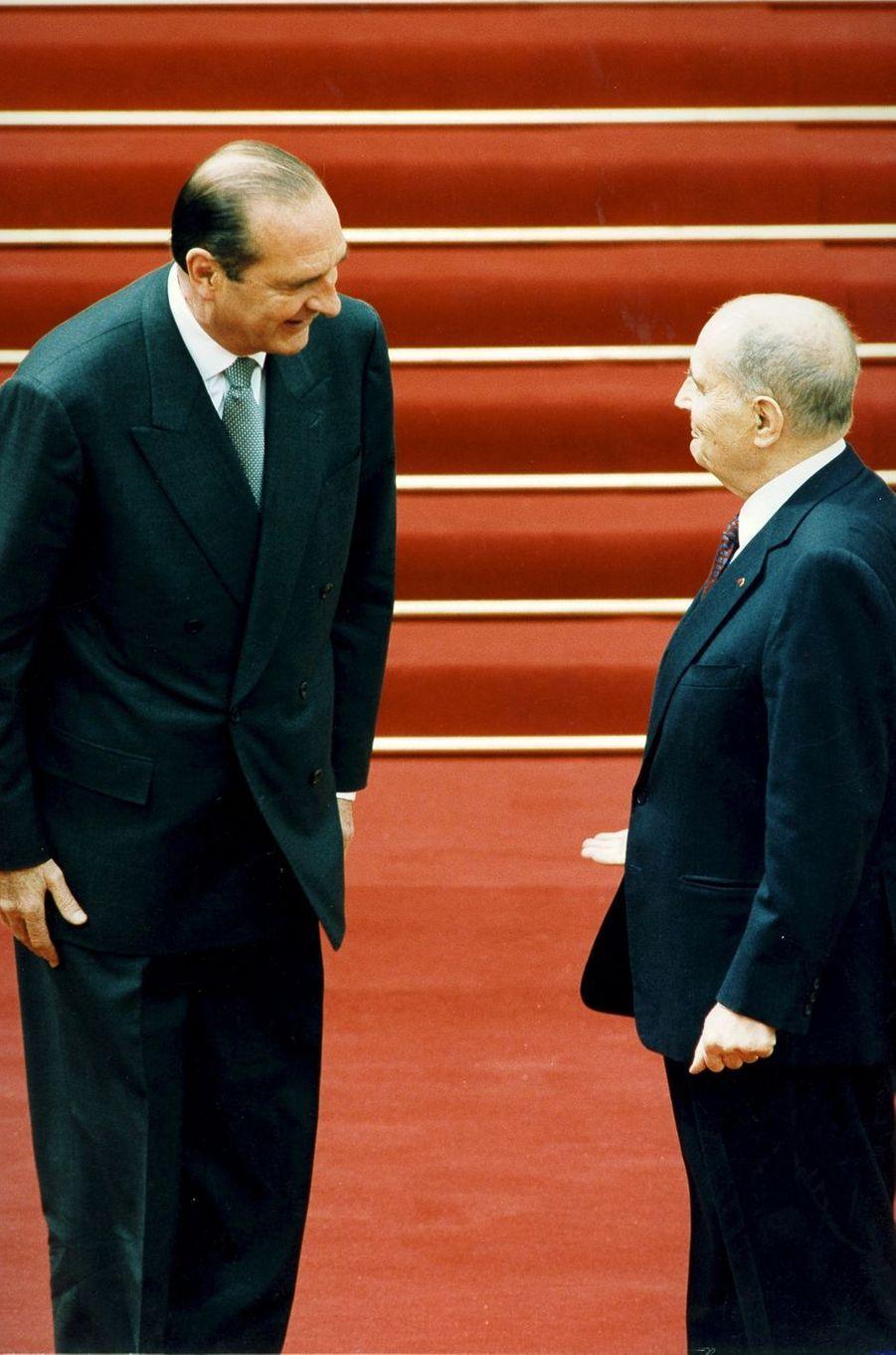 17 mai 1995.La passation des pouvoirs entre le président sortant François Mitterrand et le président élu Jacques Chirac à l'Elysée : les deux hommes se sourient sur le tapis rouge après la cérémonie à l'intérieur du palais.