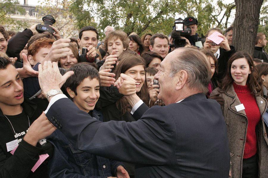 11 novembre 2005.Bain de foule pour Jacques Chirac souriant, serrant les mains de jeunes après les cérémonies du 87ème anniversaire de l'armistice de 1918 à l'Arc de Triomphe à Paris.