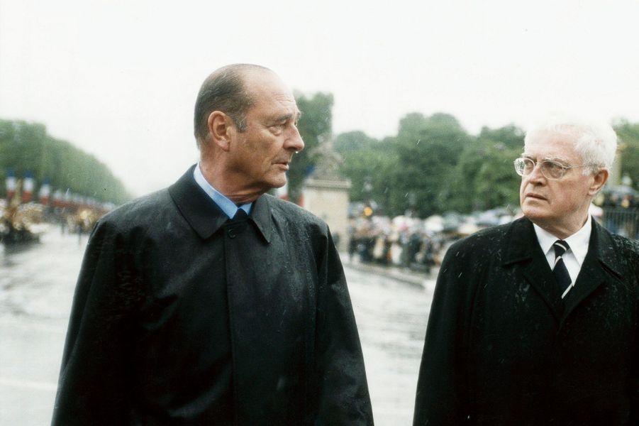 Défilé du 14 juillet 2001 à Paris : échange de regard glacial entre Jacques Chirac et son Premier ministre Lionel Jospin sous des trombes d'eau place de la Concorde en présence du ministre de la Défense Alain Richard.