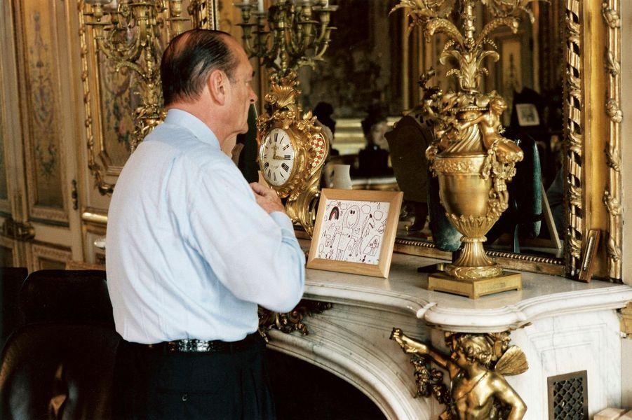 5 mai 2002.Jacques Chirac dans son bureau de l'Elysée le jour du deuxième tour des élections présidentielles 2002 : de trois-quart dos, vérifiant son noeud de cravate devant le miroir. Sur la cheminée, dans le cadre, des dessins de son petit-fils Martin.