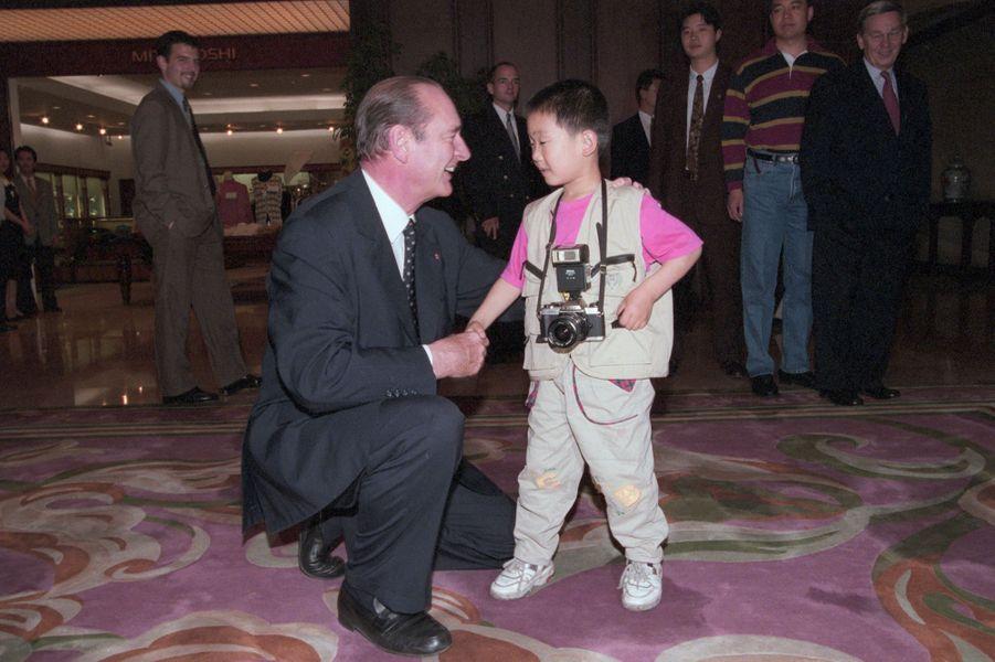 Mai 1997. Lors de son voyage officiel à Shanghaï, Jacques Chirac agenouillé et serrant la main de Zheng Zhiyu, garçon chinois et petit reporter avec son appareil photo en bandoulière, dans le hall de l'hôtel Garden.