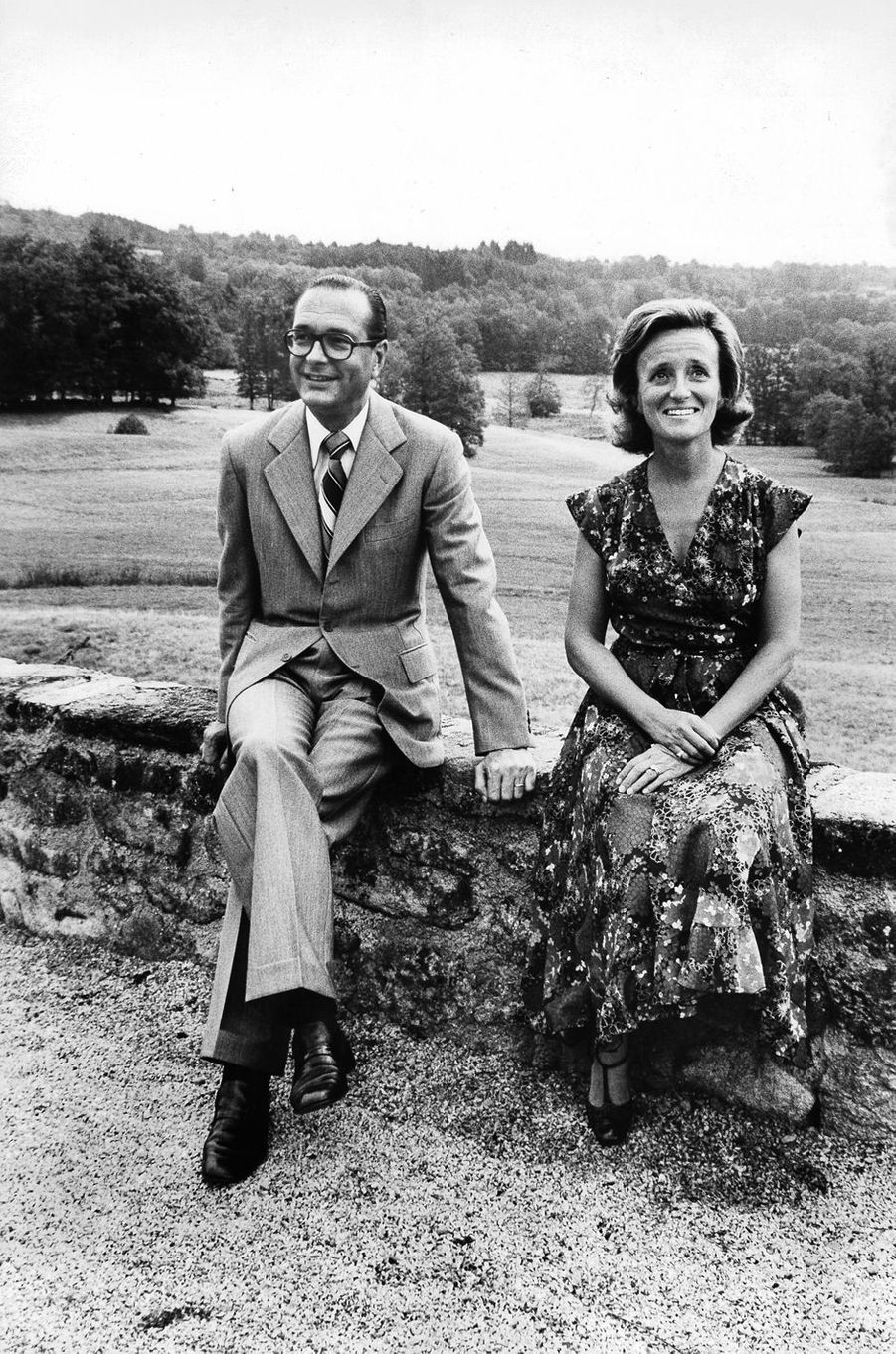 Jacques Chirac et son épouse Bernadette assis sur un muret dans le parc de leur châteaude Bitty, à Sarran, en Corrèze.