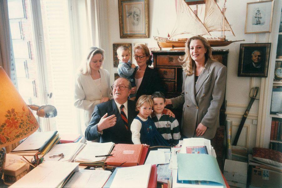 Close-up de Jean-Marie Le Pen en famille chez lui dans sa maison du parc de Montretout à Saint Cloud, le 16 mars 1995. Dans son bureau, autour de lui, ses trois filles et ses petits-enfants, de gauche à droite : Marie-Caroline, 35 ans ; Yann, 31 ans avec son fils Romain, 18 mois, et, devant elle, sa fille Marion, 5 ans; Quentin, 7 ans, fils de Marie-Caroline; Marine, 27 ans.