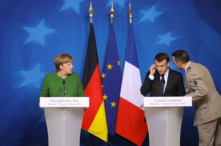 23 mars 2018.Lors d'une conférence de presse commune avec Angela Merkel à Bruxelles, Emmanuel Macron est informé par son aide de camp de l'évolution de l'attaque de Trèbes.
