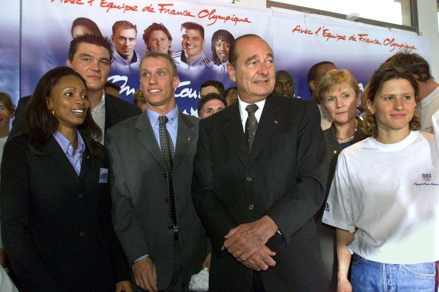 Le présidentJacques Chirac et la ministre des SportsMarie-George Buffet , en mars 2000, aux côtés deLaura Flessel, David Douillet, Florian Rousseau et Roxana Maracineanu, dans le cadre d'une campagne de soutien aux athlètes français s'apprêtant à participer aux Jeux d'été de Sydney quelques mois plus tard.