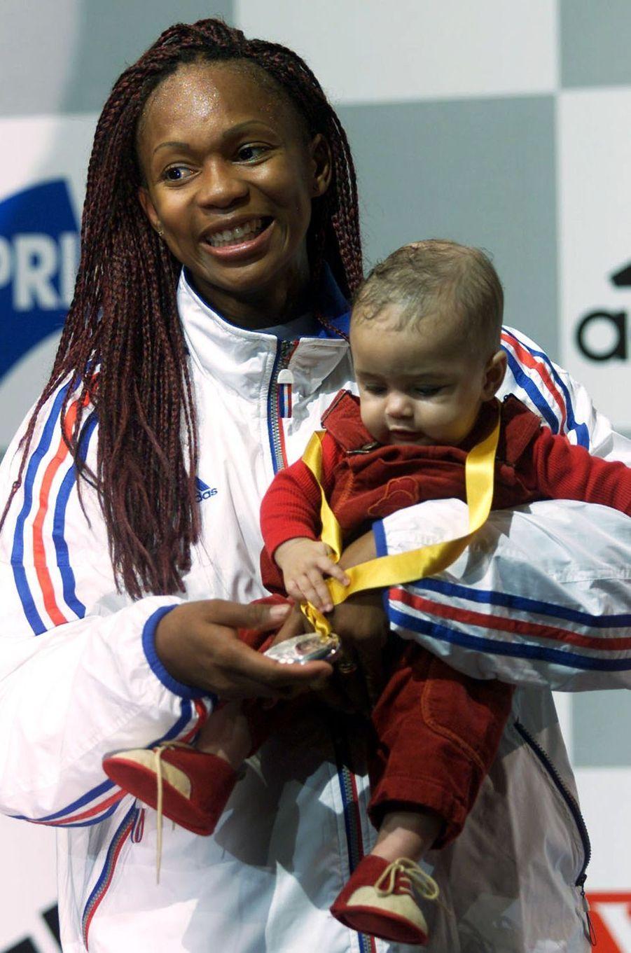 Aux championnats du monde 2001, Laura Flessel pose avec sa médaille d'argent et sa filleLeïlou.