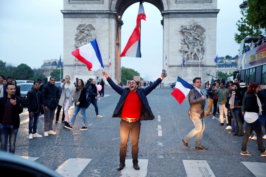 Un homme célèbre la victoire d'Emmanuel Macron sur les Champs Elysées.