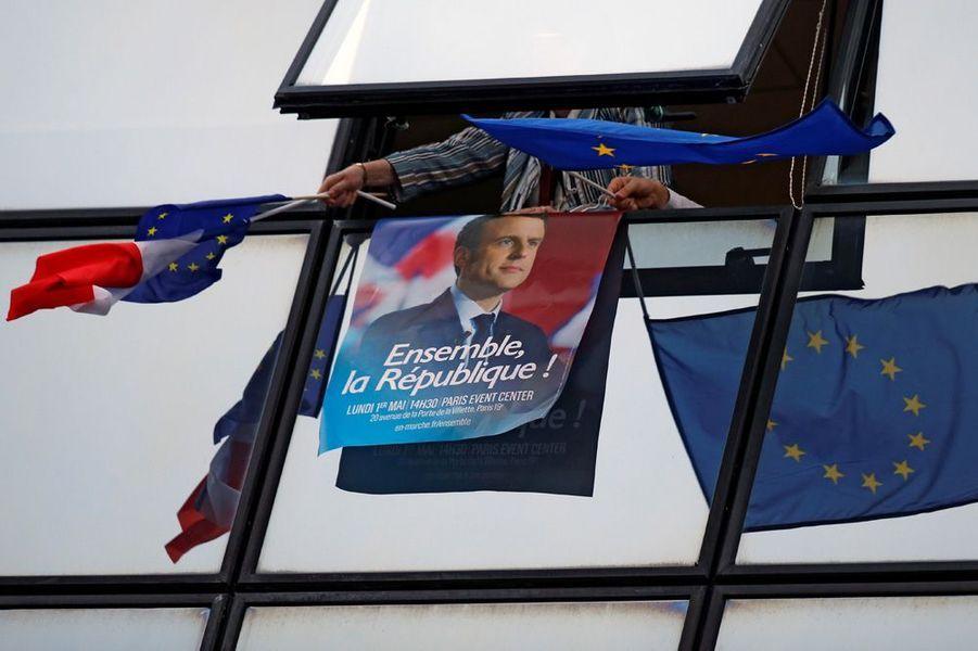 A Paris, un partisan d'Emmanuel Macron salue la victoire avec un drapeau français et un drapeau européen.