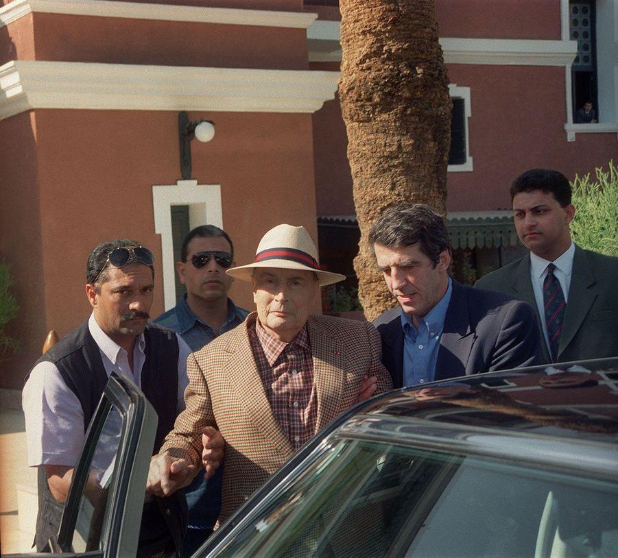 Accompagné de son médecin, le docteur Jean-Pierre Tarot, François Mitterrand quitte son hôtel pour se rendre à l'aéroport d'Assouan en Egypte. Ce cliché, pris le 29 décembre 1995, est l'un des derniers du président avant sa mort.