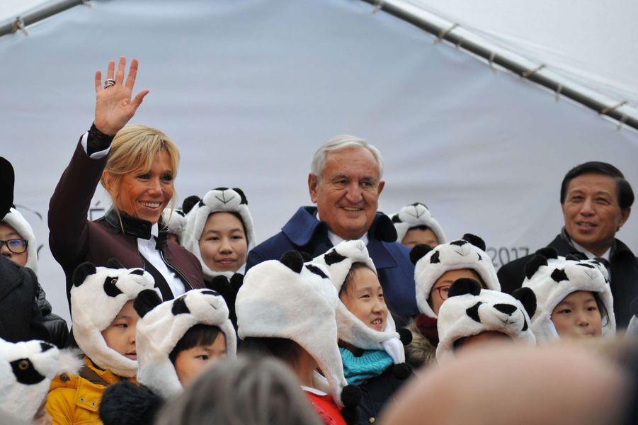 Des enfants avec des bonnets panda entourent Brigitte Macron, Jean-Pierre Raffarin etZhang Yesui.