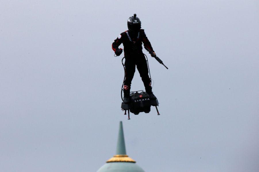 """Le champion du monde de jet-ski français Franky Zapata a offert un époustouflant spectacle futuriste en volant debout, fusil en main, à plusieurs dizaines de mètres au-dessus du sol sur son """"Flyboard"""", un engin de son invention, au-dessus des Champs-Elysées."""