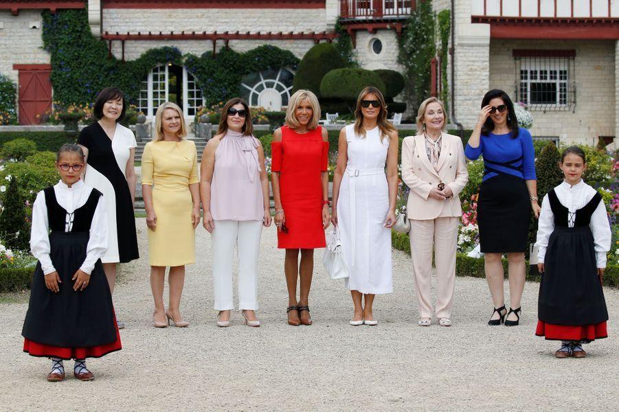 Akie Abe, Małgorzata Tusk,Jenny Morrison, Brigitte Macron,Melania Trump, Cecilia Morel etAdele Malpass posent devant la villa Arnaga, maison d'Edmond Rostand et musée dédié à l'écrivain.