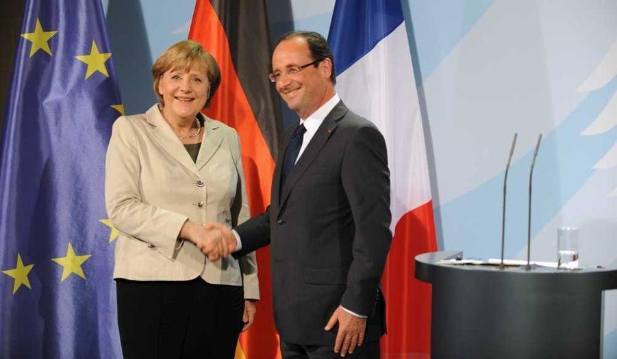 """A peine investi, François Hollande s'est envolé pour Berlin pour rencontrer Angela Merkel. Crise de la Grèce oblige, les dirigeants français et allemand, qui ont fait office de leader sous la présidence sarkozyste, devaient se rencontrer pour accorder leurs violons, alors que le premier souhaiterait tout miser sur la croissance, quand la seconde exige avant tout la discipline budgétaire. Lors d'une conférence de presse commune à la chancellerie, la chancelière et le président se sont efforcés de paraître sur la même longueur d'ondes, prônant notamment le maintien d'Athènes dans la zone euro. """"Tout doit être mis sur la table par les uns comme par les autres, tout ce qui peut contribuer à la croissance"""" lors du sommet informel du 23 mai, a déclaré Hollande, évoquant les euro-obligations ou l'utilisation des fonds structurels européens. """"Ensuite, nous en tirerons les conclusions en termes d'instruments juridiques nécessaires"""", a-t-il ajouté. Merkel s'est quant à elle dite persuadée que Paris et Berlin sauraient """"trouver une solution aux différents problèmes""""."""