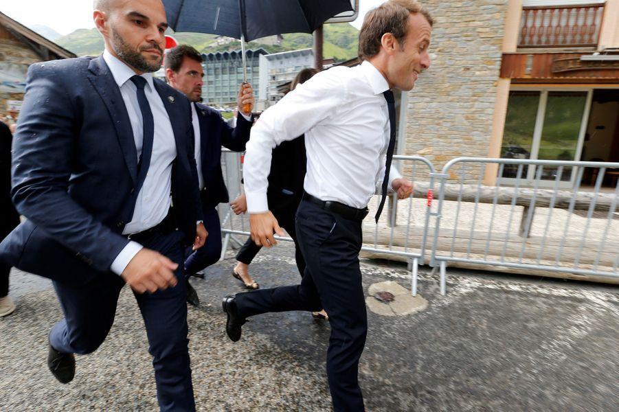 Emmanuel Macron tente d'échapper à une averse après sa visite au Pic du Midi.