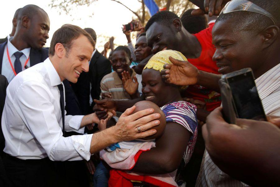 Emmanuel Macron salue une femme et son enfant, devant l'écoleLagem Taaba, à Ouagadougou.