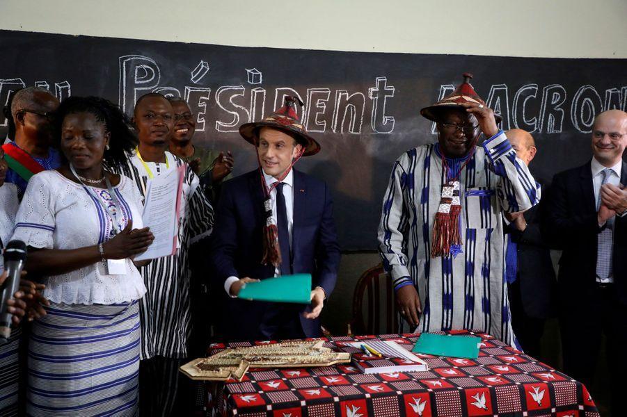 Les deux présidents portent un chapeau traditionnel, lors de la visite de l'écoleLagem Taaba, à Ouagadougou.
