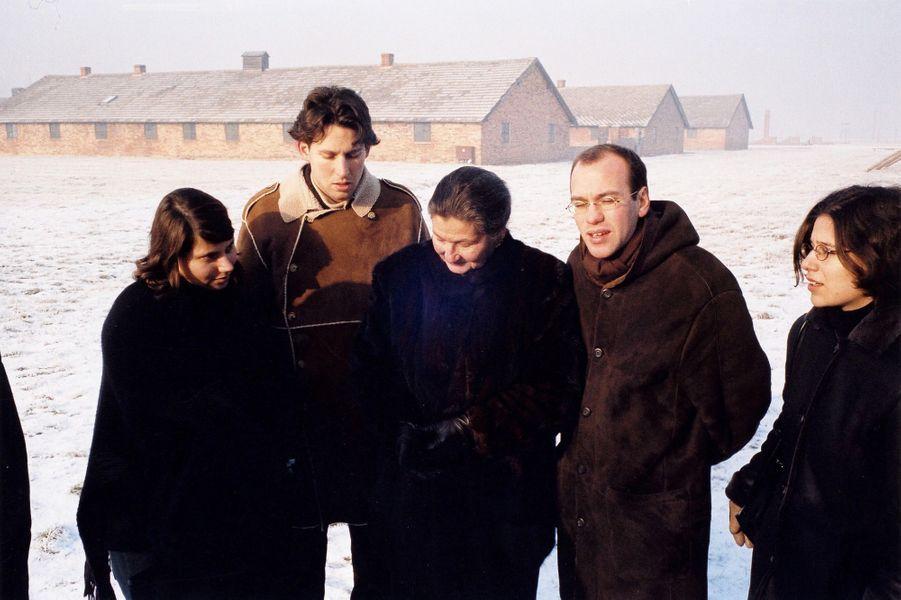 """En décembre 2004, 60 ans après sa libération, Simone Veil emmène sa famille dans le camp de concentration d'Auschwitz-Birkenau, en Pologne. Très émue à la sortie de son ancien """"bloc"""", elle est entourée de ses petits-enfants."""