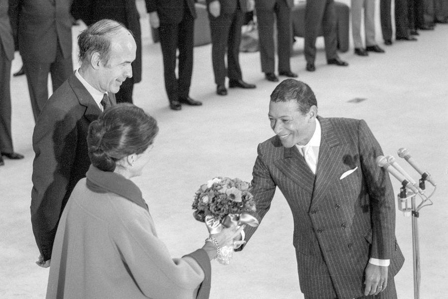 Henri Salvador offre des fleurs à Anne-Aymone Giscard d'Estaing sous le regard de Valéry Giscard d'Estaing avant le départ du président et de sa femme pour les Antilles, Orly le 12 décembre 1974, France.