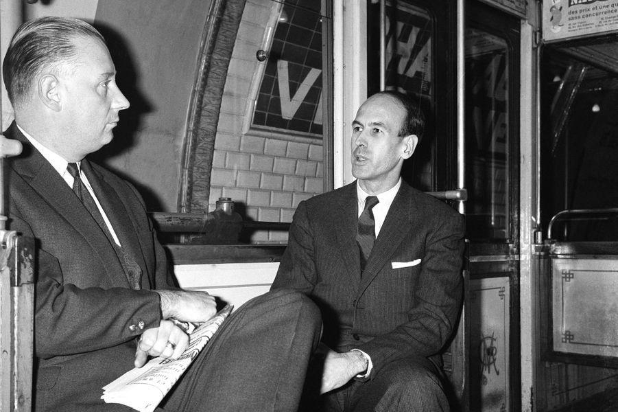 Valéry Giscard d'Estaing assis dans le métro en compagnie de Michel Poniatowski à Paris, France, en février 1964.