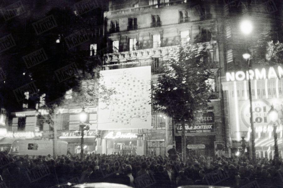 Les résultats du référendum sur la constitution de la Vème République, donnés sur une carte géante de la France, dressée sur une façade de l'avenue des Champs-Elysées, à Paris, dans la nuit du 28 au 29 septembre 1958.