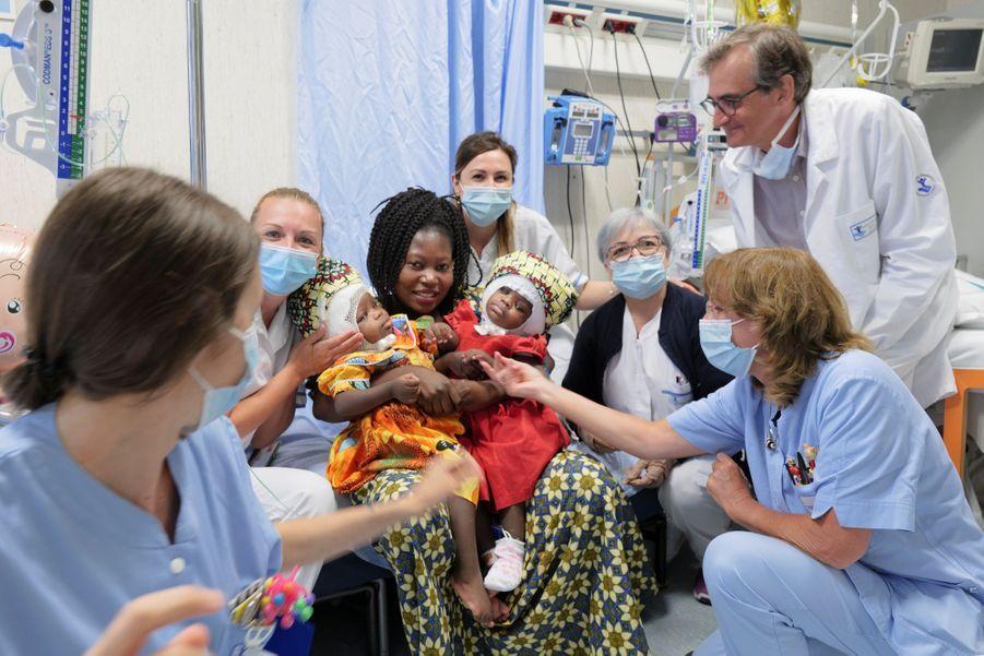 Ermine et ses deux enfants dans les bras, entourée de l'équipe médicale.