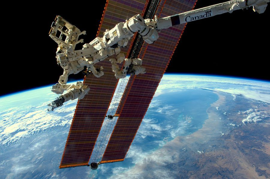 Le bras robotique Canadarm devant la Terre